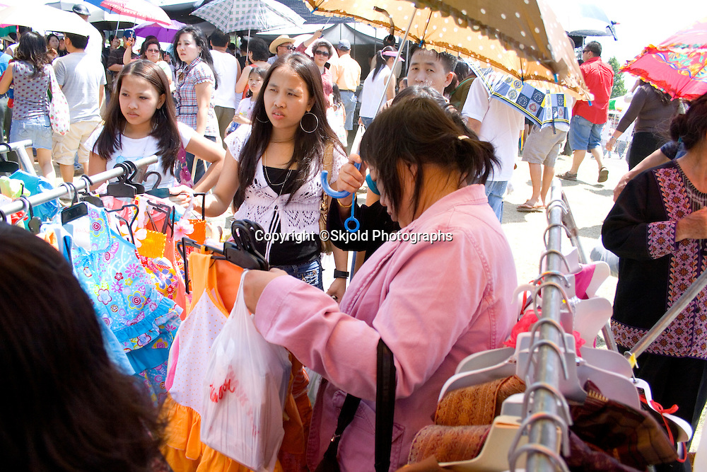 Mom shopping for traditional Hmong clothing for her disinterested young daughters. Hmong Sports Festival St Paul Minnesota USA