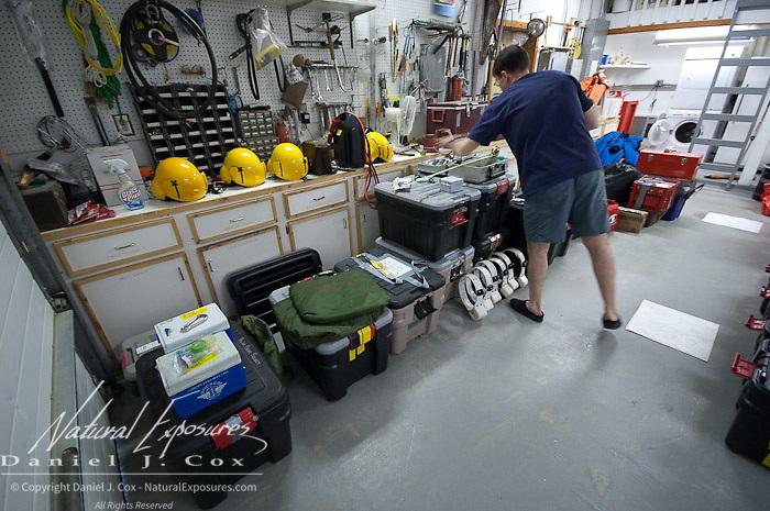 Geoff York, USGS biologist organizing field gear in the garage of the field research station in Kaktovik, Alaska.