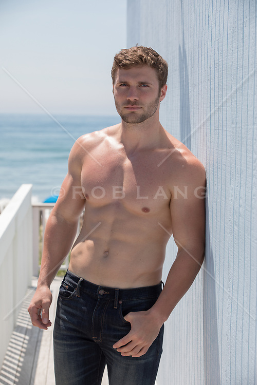muscular man in a towel on a deck shirtless good looking man in jeans by the ocean