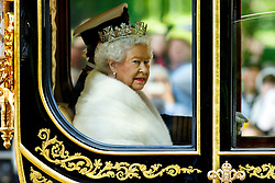 © Licensed to London News Pictures. 27/05/2015. London, UK. Queen Elizabeth II being driven down The Mall in a horse drawn carriage to attend the State Opening of Parliament on May 27, 2015 in London. In a speech to Members of Parliament and Peers in The House of Lords, Queen Elizabeth II will officially open a new session of parliament, which will set out the government's agenda and legislation for the coming year. Photo credit : Tolga Akmen/LNP