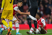 Gabriel Martinelli (Arsenal) assisting Joe Willock (Arsenal) to his feet during the Europa League match between Arsenal and Standard Liege at the Emirates Stadium, London, England on 3 October 2019.