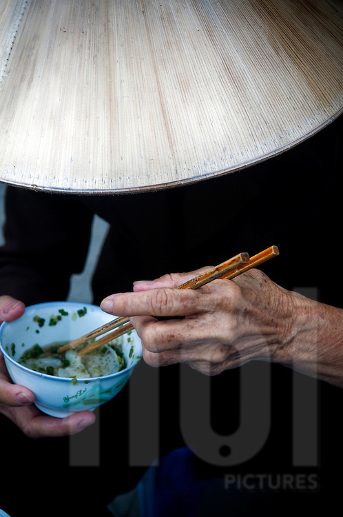 On Doc Let market in Khanh Hoa province, an elderly vietnamese woman is eating a soup, hidden under her traditional conical hat, this person is unrecognizable.