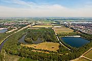 Nederland, Noord Brabant, Gemeente Waalwijk, 08-07-2010. Vroegere Baardwijksche Overlaat, strook land tussen Waalwijk (links) en Drunen. Bij hoog water vormde de overlaat een extra afvoer voor het water van de Maas. Aan de horizon de Bergsche Maas waar de overlaat in uitmondde. Links het afwateringskanaal 's-Hertogenbosch - Drongelen. Dit kanaal heeft de overlaat vervangen. .Baardwijksche Overlaat, strip of land between Waalwijk (left) and Drunen, used as spillway (additional outlet for the water of the Meuse). On the horizon the Bergsche Maas..luchtfoto (toeslag), aerial photo (additional fee required).foto/photo Siebe Swart.