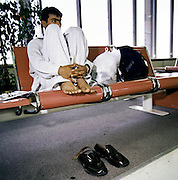 With feet up on airport seating, a migrant worker awaits his homeward flight from Bahrain to South-Asia. Sitting with legs gathered and with shoes removed - in the manner that people subjected to fierce desert or tropical heat try to keep cool, although in this airpirt terminal building, air-conditioning allows more comfort. The young man works on building projects somewhere in the middle-east region and is either in transit of beginning his journey to India, Pakistan or perhaps Bangladesh, seen here months before the terrorist attacks on America that changed the public's attitude to flying on commercial airliners.