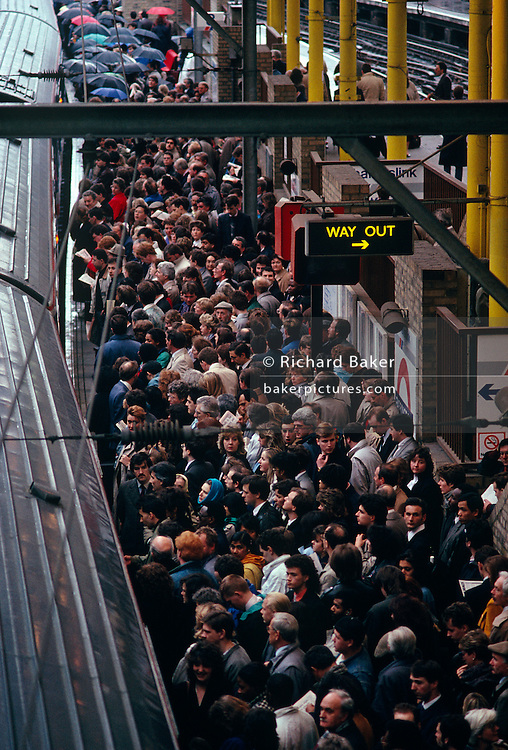 During the evening rush hour, hundreds of rail commuters are queueing to board a Thameslink train which has just arrived on the platform at Farringdon Station in Clerkenwell, London England. Standing 10-deep, they patiently wait the next ride home southbound during a tube strike forced the closure of underground stations and making workers take alternative routes. Looking down from a high bridge we see the train's roof and the heads of those delayed and inconvenienced. It is another miserable journey home.