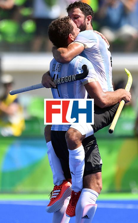 Argentina's Manuel Brunet (top) celebrates with Argentina's Juan Gilardi (bottom) during the men's quarterfinal field hockey Spain vs Argentina match of the Rio 2016 Olympics Games at the Olympic Hockey Centre in Rio de Janeiro on August 14, 2016. / AFP / Carl DE SOUZA        (Photo credit should read CARL DE SOUZA/AFP/Getty Images)