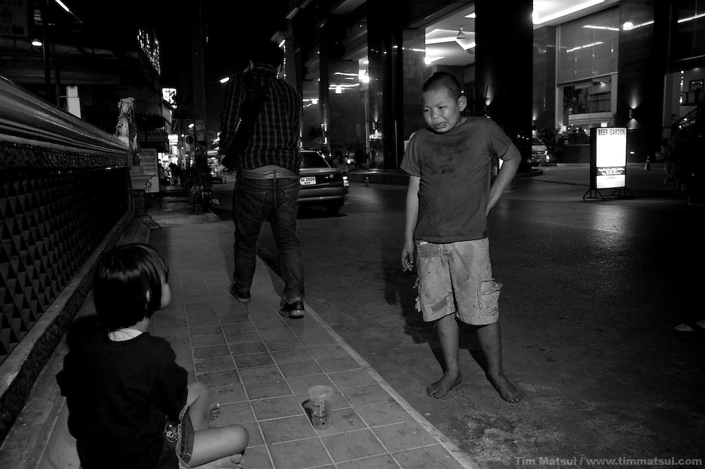 Oahn (fatty), a homeless street kid, eyes a young girl begging late at night on the streets of Chiang Mai in the red light district; her mother, with baby, is across the street also begging..Members of the Volunteer for Children's Development Foundation (VGCD) work the streets near the sex worker bars, talking with young prostitutes and street children about the opportunities their organization offer such as counseling, life skills training, emergency assistance, and temporary shelter. Many of VGCD's volunteers have been or still are sex workers who, while working, will watch for sexual and commercial exploitation of minors. According to VGCD members, children are often sent to beg or sell flowers to tourists in the bars; exposure to a highly sexualize atmosphere until the early hours of the morning puts the children at risk for exploitation and many wind up working in the sex industry either as juveniles or later as adults..