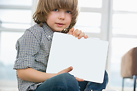 Portrait of cute boy showing his drawing on digital tablet at home