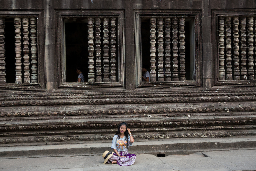 An Asian woman sits and rests besides beautiful stone carvings decorating a walkway within a gallery in Angkor Wat temple complex Siem Reap, Cambodia.  Angkor Wat is one of UNESCO's world heritage sites. It was built in the 12th century and covers 162 hectares.  It is Cambodia's main tourist attraction.  (photo by Andrew Aitchison / In pictures via Getty Images)