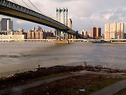 View of The Manhattan Bridge with an empty parking lot on the foreground.