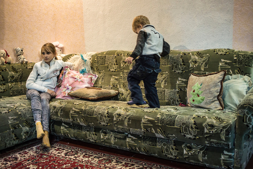 DNIPROPETROVSK, UKRAINE - OCTOBER 12: Yeva (L) sits on the couch in the home where she, her mother, and her grandmother are living with a family in their church's congregation after fleeing fighting in Luhansk in Eastern Ukraine while her host brother Ilya plays on October 12, 2014 in Dnipropetrovsk, Ukraine. The United Nations has registered more than 360,000 people who have been forced to leave their homes due to fighting in the East, though the true number is believed to be much higher.(Photo by Brendan Hoffman/Getty Images) *** Local Caption ***