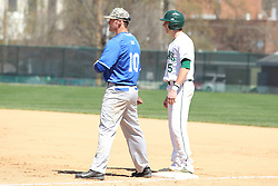 11 April 2015:  Tim Coonan stands on first next to first baseman Erik Schurtz during an NCAA division 3 College Conference of Illinois and Wisconsin (CCIW) Pay in Baseball game during the Conference Championship series between the Millikin Big Blue and the Illinois Wesleyan Titans at Jack Horenberger Stadium, Bloomington IL