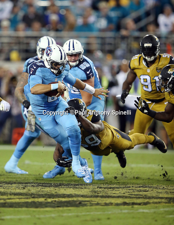 Tennessee Titans quarterback Marcus Mariota (8) gets sacked by diving Jacksonville Jaguars defensive end Ryan Davis (59) late in the second quarter during the 2015 week 11 regular season NFL football game against the Jacksonville Jaguars on Thursday, Nov. 19, 2015 in Jacksonville, Fla. The Jaguars won the game 19-13. (©Paul Anthony Spinelli)