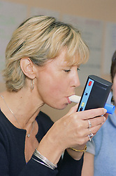 Woman blowing into device to monitor carbon monoxide levels during antismoking training session,