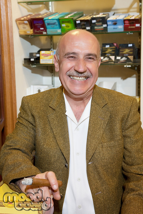 Portrait of a happy mature owner of tobacco shop smoking cigar