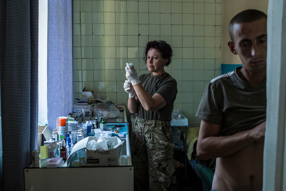 MELEKYNE, UKRAINE - AUGUST 30, 2015: A medic prepares an injection for a fighter of the Donbass Battalion, a pro-Ukraine militia that has been integrated into the National Guard, at their base in Melekyne, Ukraine. Many of the formerly autonomous battalions have recently been pulled back from the front line and replaced by regular Ukrainian soldiers, which has frustrated some of the fighters, who consider themselves battle-tested and eager to continue the fight. CREDIT: Brendan Hoffman for The New York Times