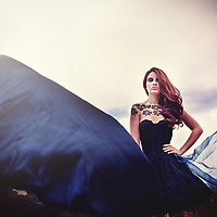 Fabric billowing and floating around a young woman in black and lace