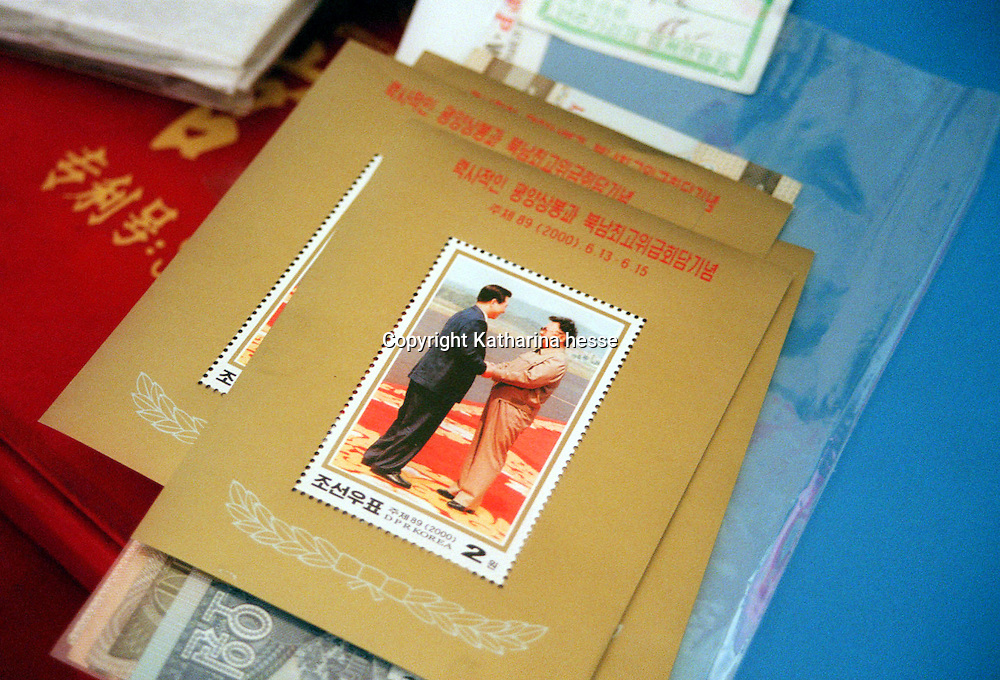"""TUMEN, CHINA - OCTOBER 20: Stamps of a meeting between the two leaders of North and South Korea are seen for sale in a souvenir shop October 20, 2002 in China. North Korean nationals fleeing starvation or even sometimes imprisonment, usually are refused entry to China, and if caught, forcibly repatriated. Although China signed a treaty, the Chinese government considers the refugees as """"economic migrants,"""" and rejects arguments that the North Koreans are fleeing a repressive government whose policies have caused millions to die. Despite this official policy, however, in the frozen woods and rivers that separate China and North Korea, in recent years thousands have snuck across to freedom, helped by aid workers and sympathetic locals. Refugees as well as those who help them keep a low profile and remain anonymous."""