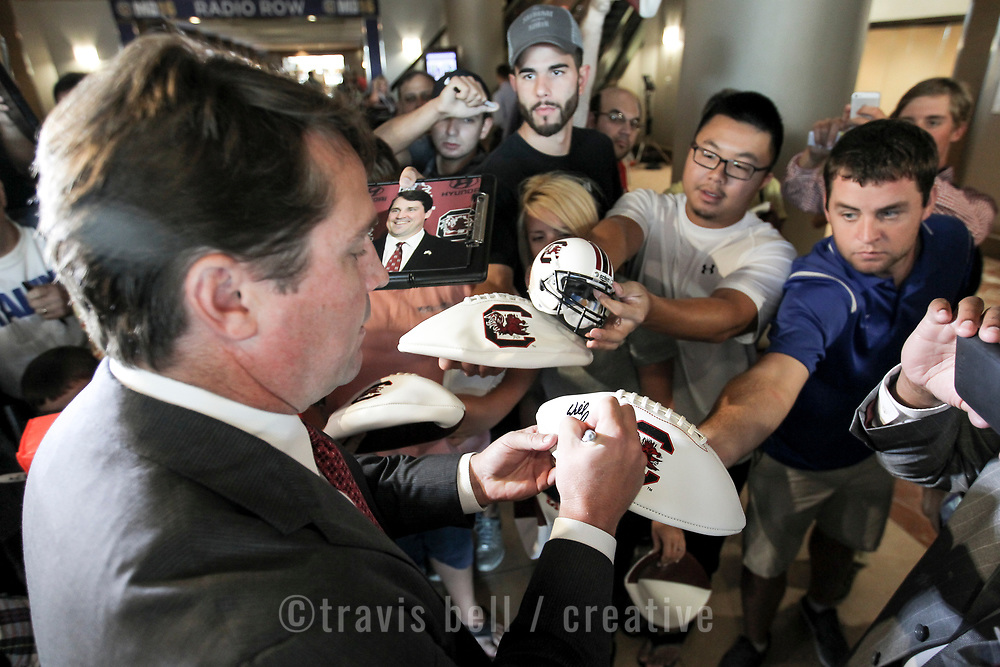 Muschamp is swarmed in the lobby of the hotel after arriving and asked for autographs. Fans are allowed inside the lobby throughout the event and many seek out coaches and players when they arrive. ©Travis Bell Photography