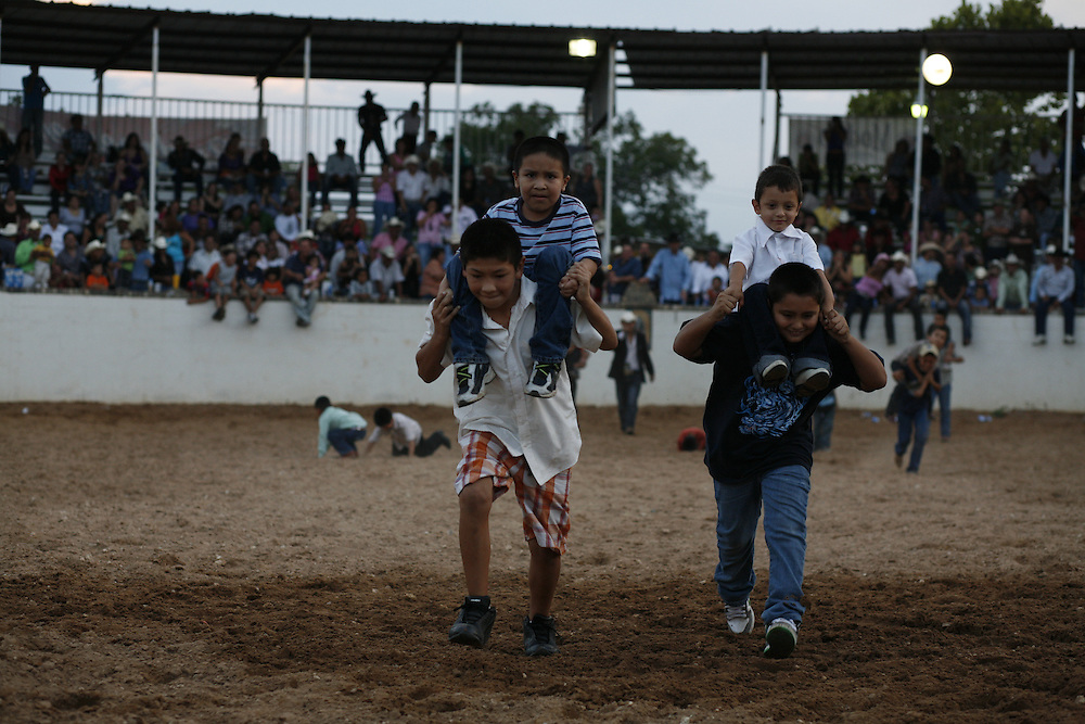 Photo by Julia Robinson.Children race through the lienzo during a break from the action at El Bajio in Von Ormy, Texas.  The charreada is a family event and lienzos in central Texas strive to make it entertaining for everyone.  Mariachis and ballet folklorico troupes are common additions to the suertes.