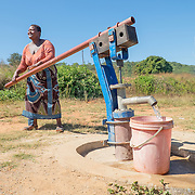 CAPTION: Maria pumps water from one of the newly installed borehole pumps. These pumps are much easier for women and children to use, as the are significantly less heavy. LOCATION: Near Bikita Rural Hospital, Bikita District, Masvingo Province, Zimbabwe. INDIVIDUAL(S) PHOTOGRAPHED: Maria Chagwiza.
