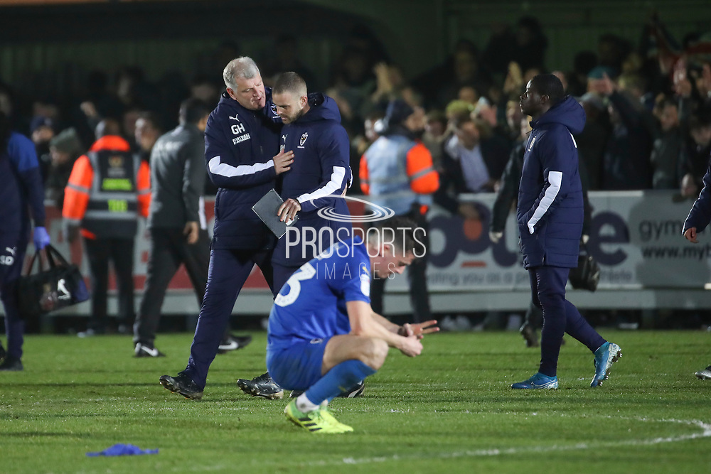AFC Wimbledon manager Glyn Hodges talking to AFC Wimbledon fitness coach Jason Moriarty who is his last game and AFC Wimbledon midfielder Callum Reilly (33) kneeling down during the EFL Sky Bet League 1 match between AFC Wimbledon and Southend United at the Cherry Red Records Stadium, Kingston, England on 1 January 2020.