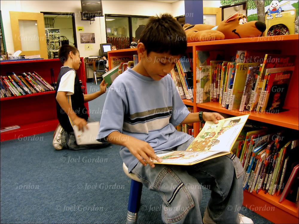 Elementary scene, Hispanic American student reading in library