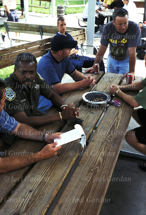 African American Correction Officer talking to inmates sitting in rec yard of Orange County Jail Work (halfway house ) Release Center in Orlando FL