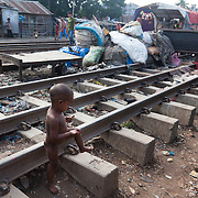 Life in the slums by the  railway tracks in Tejgaon. Homes are build closely to the tracks leading in and out of one of Dhaka's main train stations and life is goes on as in any othr part of Dhaka in spite of the dangerous proximity to the live tracks and trains passing at regular intervals. A small child is playing with a lip stick on the tracks.
