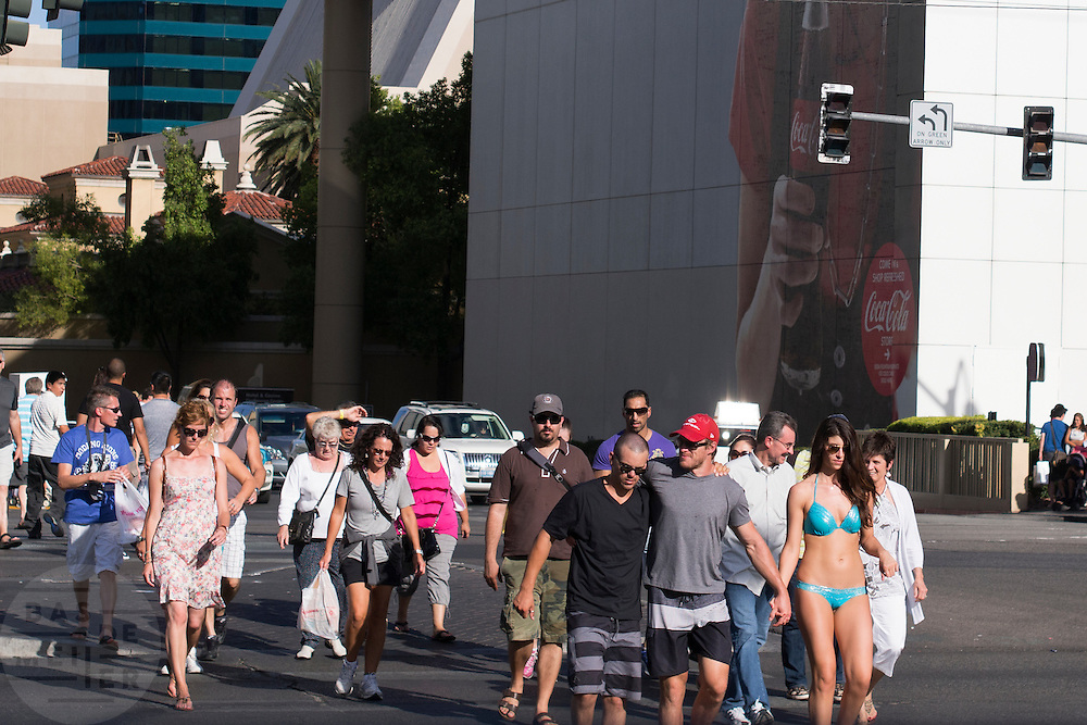 Een vrouw in bikini loopt met een groep mannen over de strip in Las Vegas.<br /> <br /> A woman wearing a bikini is walking with a group of men at the strip in Las Vegas.