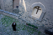 A nun looks up from the courtyard at Säben Abbey in Klausen, South Tyrol, Italy. Säben Abbey is a Benedictine nunnery established in 1687, when it was first settled by the nuns of Nonnberg Abbey in Salzburg.