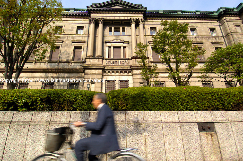 Office worker in formal suit cycles in front of Bank of Japan headquarters in Tokyo Man cycles in front of Bank of Japan headquarters in Tokyo