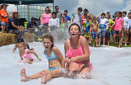 Maggie Coyle, 9, and Haley Riley, 10, connect as they speed down the giant Slip 'N Slide courtesy of Home Depot on Saturday at the 10th annual Spring Hill Pay It Forward Festival.