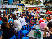 "18 MAY 2017 - BANGKOK, THAILAND: A worker seats customers at a street food stall in Bangkok's Chinatown. City officials in Bangkok have taken steps to rein in street food vendors. The steps were originally reported as a ""ban"" on street food, but after an uproar in local and international news outlets, city officials said street food vendors wouldn't be banned but would be regulated, undergo health inspections and be restricted to certain hours on major streets. On Yaowarat Road, in the heart of Bangkok's touristy Chinatown, the city has closed some traffic lanes to facilitate the vendors. But in other parts of the city, the vendors have been moved off of major streets and sidewalks.      PHOTO BY JACK KURTZ"