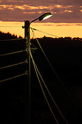 burning streetlight and above ground electric cables against an orange sky