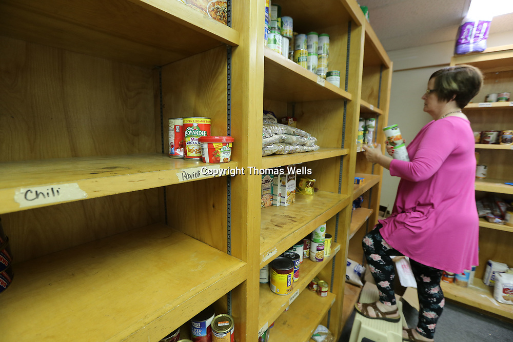 Susan Gilbert uses what canned food she has left to stock the shelves at the Salvation Army food pantry.