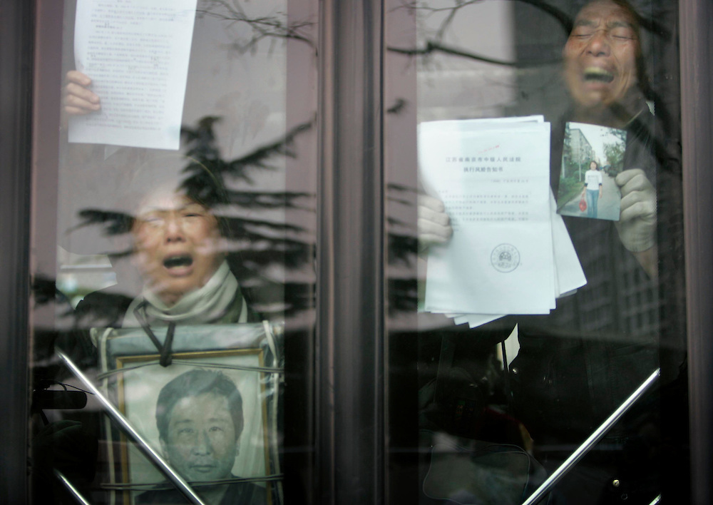 Protesters show letters detailing their complaints and asking for justice as they are taken away by police outside of the Foreign Ministry  Beijing, China, Wednesday, Dec.10, 2008. Two dozen people held a bold protest using the 60th anniversary of the declaration of human rights to decry a myriad of alleged government abuses.