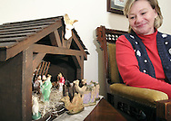 "Peggy Thoma, at her Piqua home, looks at a Nativity Scene made by her father, using the wooden box that he used to ship things home from Korea. Thoma says that, ""each neighbor on the street then bought a figure to furnish the complete manger."""