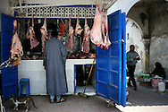 Morocco, Essaouira. Man buying meat at the butcher's.