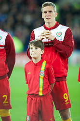 CARDIFF, WALES - Friday, October 12, 2012: A mascot stands in front of Wales' Steve Morison before the Brazil 2014 FIFA World Cup Qualifying Group A match against Scotland at the Cardiff City Stadium. (Pic by David Rawcliffe/Propaganda)