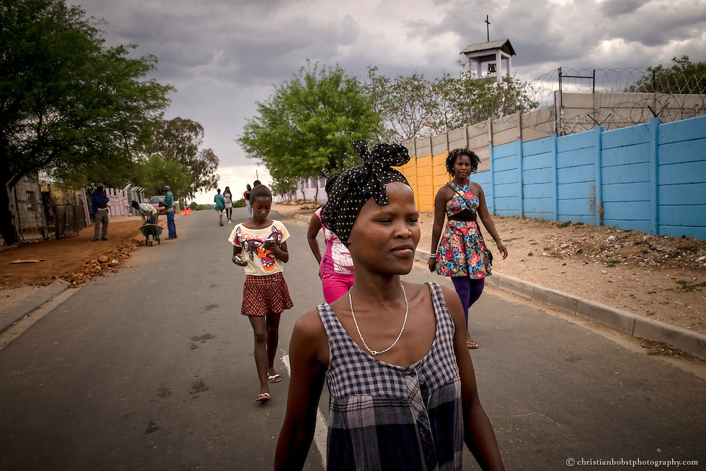 (2013) A couple of girls walk down the street  at Damara 6. They often stay together as a group. Sex workers in Katutura cannot count on the solidarity of their neighbors or relatives; they usually only get help from other girls who do the same work in order to survive.