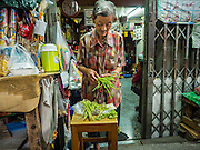 10 SEPTEMBER 2015 - BANGKOK, THAILAND: A woman sorts vegetables in front of her home  on Thetsaban Sai 1 Road, a pedestrian footpath next to Wat Kalayanamit. The woman's home, and other homes on the path, are scheduled to be demolished in the next week. Authorities started to destroy 54 homes in front of Wat Kalayanamit, a historic Buddhist temple on the Chao Phraya River in the Thonburi section of Bangkok. Government officials, protected by police, seized the house of Chaiyasit Kittiwanitchapant, a Kanlayanamit community leader, who has led protests against the temple's abbot for trying to evict community members whose houses are located around the temple. Work crews went into Chaiyasit's home and took it apart piece by piece. The abbot of the temple said he was evicting the residents, who have lived on the temple grounds for generations, because their homes are unsafe and because he wants to improve the temple grounds. The evictions are a part of a Bangkok trend, especially along the Chao Phraya River and BTS light rail lines, of low income people being evicted from their long time homes to make way for urban renewal.     PHOTO BY JACK KURTZ