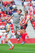 Paul Downing (#5) of Portsmouth FC and Charlie Wyke (#9) of Sunderland AFC compete for a header during the EFL Sky Bet League 1 match between Sunderland and Portsmouth at the Stadium Of Light, Sunderland, England on 17 August 2019.