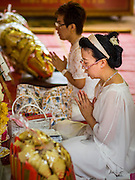 28 AUGUST 2015 - BANGKOK, THAILAND: Women participate in a Hungry Ghost Day prayer at Wat Mangkon Kamalawat in the Chinatown section of Bangkok. Wat Mangkon Kamalawat is the largest Mahayana Buddhist temple in Chinatown. Mahayana  Buddhists believe that the gates of hell are opened on the full moon of the seventh lunar month of the Chinese calendar, and the spirits of hungry ghosts allowed to roam the earth. These ghosts need food and merit to find their way back to their own. People help by offering food, paper money, candles and flowers, making merit of their own in the process. Hungry Ghost Day is observed in communities with a large ethnic Chinese population, like Bangkok's Chinatown.     PHOTO BY JACK KURTZ
