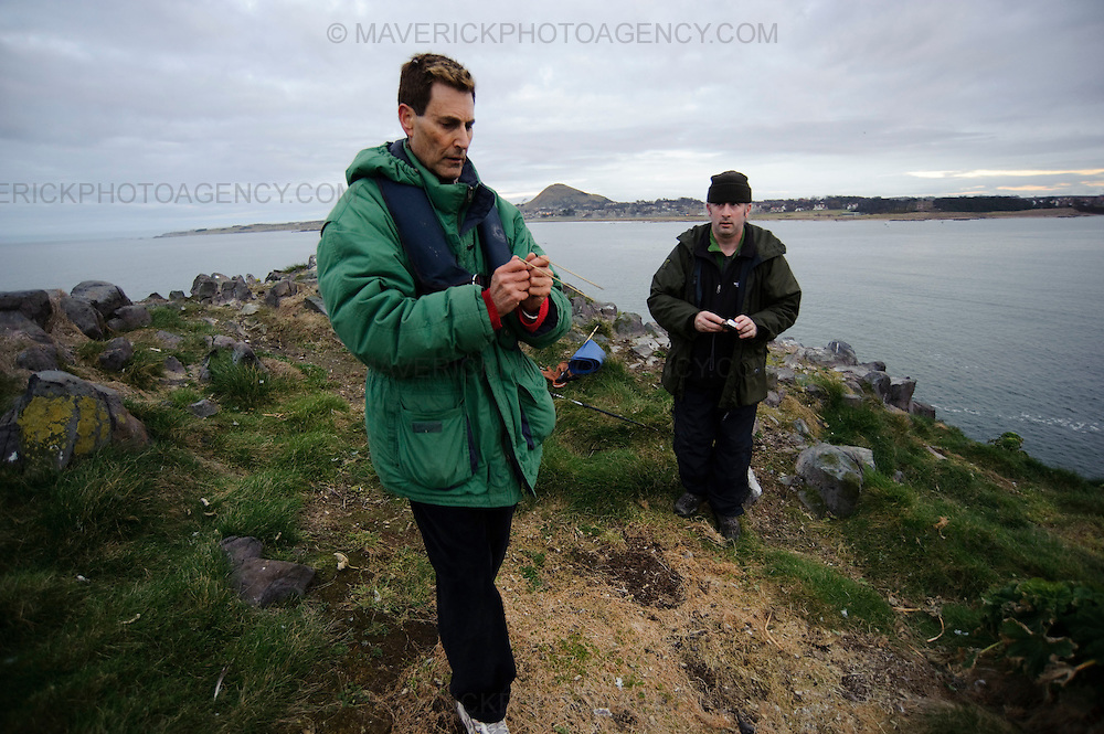 """NORTH BERWICK, UK - 6th March 2010:  Mystifier Uri Geller sets foot on Lamb island, a tiny island which is believed to be connected with the Great Pyramids of Giza, in search of treasure left behind by an exiled Egyptian Princess """"Scota"""".  Uri bought the tiny island which is situated just off North Berwick, in the Firth of Forth after his friend Mohammed Al Fayed republished """"Abbot of Inchcolm"""" a 15th Century document linking the islands to ancient Egypt. Pictured Uri uses dowsing rods to search for treasure on the island, pictured with """"Island Man"""" Andy Stranegway.   (Photograph: Callum Bennetts/MAVERICK)"""