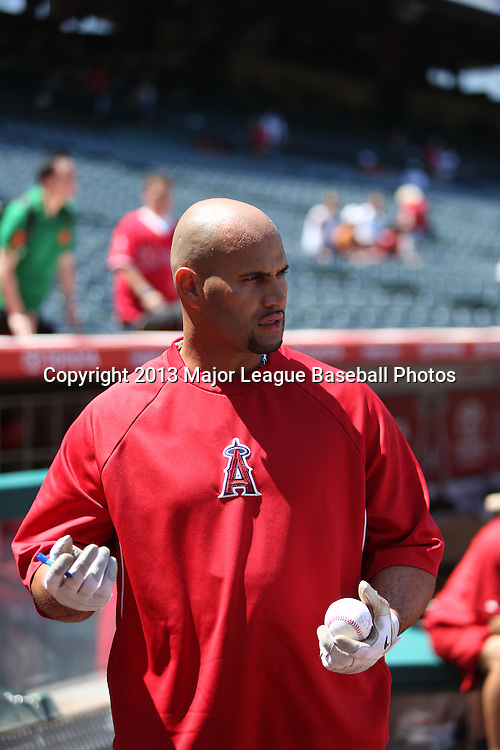 ANAHEIM, CA - JUNE 15:  Albert Pujols #5 of the Los Angeles Angels of Anaheim autographs a baseball during batting practice before the game against the New York Yankees on Saturday, June 15, 2013 at Angel Stadium in Anaheim, California. The Angels won the game 6-2. (Photo by Paul Spinelli/MLB Photos via Getty Images) *** Local Caption *** Albert Pujols