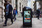 A modern London street bin showing a news image on the digital screen. The news image is of Oscar Pistorius going to court on murder charge. The bin is located on King William Street, near Bank in London, United Kingdom.
