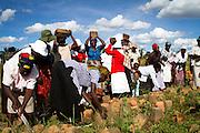 Elderly women in rural Zimbabwe carrying bricks.
