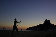 Youngsters fly kites during the late afternoon sunset on Ipanema beach, Rio de Janeiro,  Brazil. 6th July 2010. Photo Tim Clayton..The beaches of Rio de Janeiro, provide the ultimate playground for locals and tourists alike. Beach activity is in abundance as beach volley ball, football and a hybrid of the two, foot volley, are played day and night along the length and breadth of Rio's beaches. .Volleyball nets and football posts stretch along the cities coastline and are a hive of activity particularly at it's most famous beaches Copacabana and Ipanema. .The warm waters of the Atlantic Ocean provide the ideal conditions for a variety of water sports. Walkways along the edge of the beaches along with exercise stations and cycleways encourage sporting activity, even an outdoor gym is available at the Parque Do Arpoador overlooking the ocean. .On Sunday's the main roads along the beaches of Copacabana, Leblon and Ipanema are closed to traffic bringing out thousands of people of all ages to walk, run, jog, ride, skateboard and cycle more than 10 km of beachside roadway. .This sports mad city is about to become a worldwide sporting focus as they play host to the world's biggest sporting events with Brazil hosting the next Fifa World Cup in 2014 and Rio de Janeiro hosting the Olympic Games in 2016...