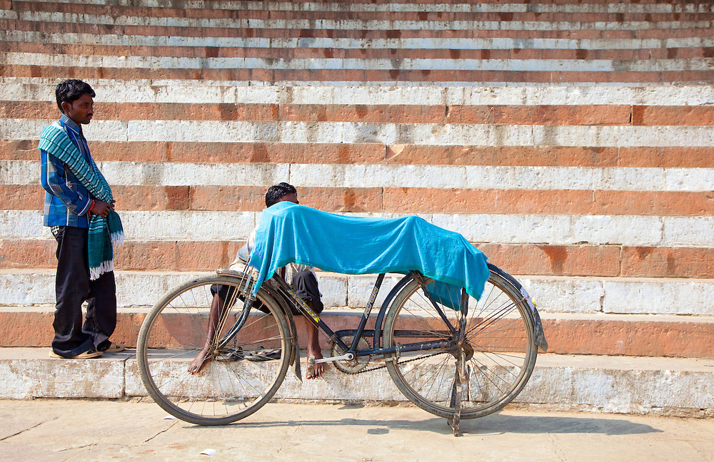 A Man Dries A Cloth On A Bicycle In Varanasi, India.